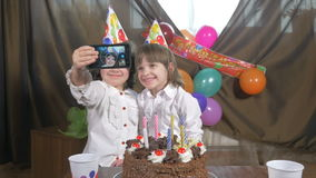 4k - Young beautiful twin girls taking a selfie (self portrait) with a smartphone at a birthday party stock footage