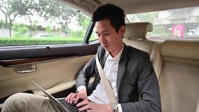4K Young businessman using laptop in back seat of car.  stock footage
