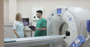 4K Young doctor and nurse discussing diagnosis on a background of a new magnetic resonance imaging. stock footage