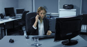 4K: A young employee sits tensely in her office. A telephone call disturbs her computer work. stock footage
