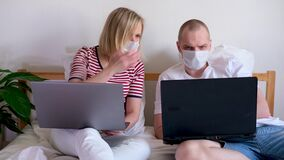 4k young family works remotely from home on bed at the computer. Quarantined couple coronavirus in medical masks. Stay