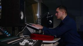 4K Young sound engineer in recording studio using laptop at the mixing desk stock video footage