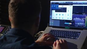 4K Young sound engineer in recording studio using laptop at the mixing desk stock video