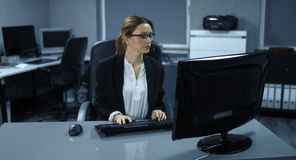 4K: A young woman sits down to her computer workstation and starts to read her mails and to answer. Besides, she is surely relaxed in a modern office stock video