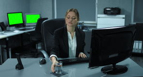 4K: A young woman is sitting at her computer. She is having a drink of water while working and takes pleasure at the work. In the background are two monitors stock video