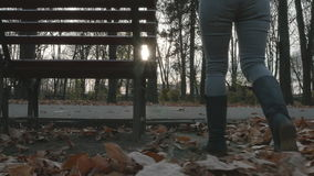 4k - Young woman walking in the park in autumn and sitting on a bench. 4k Young woman walking in the park in autumn and sitting on a bench stock video