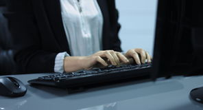 4K: A young woman writes on the computer keyboard.It is a medium shot from the keyboard and hands stock video footage