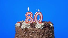4k - Zahl achtzig Geburtstagskerzen auf einem köstlichen Schokoladenkuchen, blauer Schirm heraus durchbrennen stock video
