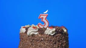 4k - Zahl drei-Geburtstags-Kerze auf einem köstlichen Schokoladenkuchen, blauer Schirm heraus durchbrennen stock video footage