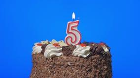 4k - Zahl fünf-Geburtstags-Kerze auf einem köstlichen Schokoladenkuchen, blauer Schirm heraus durchbrennen stock footage