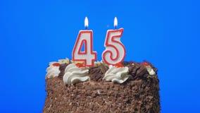 4k - Zahl fünfundvierzig Geburtstagskerzen auf einem köstlichen Schokoladenkuchen, blauer Schirm heraus durchbrennen stock video footage