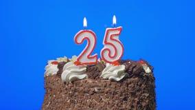 4k - Zahl fünfundzwanzig Geburtstagskerzen auf einem köstlichen Schokoladenkuchen, blauer Schirm heraus durchbrennen stock video footage