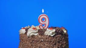 4k - Zahl neun-Geburtstags-Kerze auf einem köstlichen Schokoladenkuchen, blauer Schirm heraus durchbrennen stock video footage