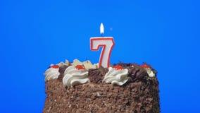 4k - Zahl sieben-Geburtstags-Kerze auf einem köstlichen Schokoladenkuchen, blauer Schirm heraus durchbrennen stock footage