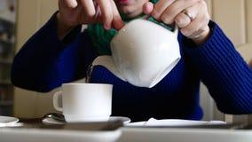 4k Zamykają w górę strzału kobiety dolewania herbaty w filiżankę od teapot zdjęcie wideo