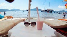 4k zbliżenia materiał filmowy okulary przeciwsłoneczni i koktajl z dwa słoma na stole między sunbeds na morze plaży zbiory