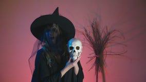 4k, Zeitlupe, Halloween Eine Frau im Kostüm einer schrecklichen Hexe tanzt mit einem Schädel in ihren Händen Kopieren Sie Platz stock video