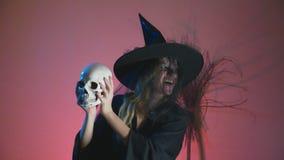 4k, Zeitlupe, Halloween Eine Frau im Kostüm einer schrecklichen Hexe tanzt mit einem Schädel in ihren Händen Kopieren Sie Platz stock video footage