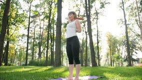 4k zwolnionego tempa wideo w ?rednim wieku u?miechni?tej kobiety ?wiczy joga i medytowa? w parku przy pogodnym letnim dniem zbiory wideo