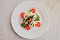Kałamarnicy i mussels z warzywami na białym talerzu na białym tle z cieniem, selekcyjnej ostrości przód, odgórny widok obraz royalty free