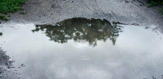 Kałuża jest po środku drogi podczas deszczu z zdjęcia stock