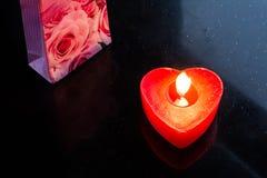 Kaars in de vorm van een hart die in dark branden stock afbeeldingen
