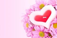 Kaars in de vorm van een hart en chrysanten. Stock Foto's