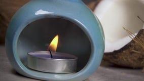 Kaars in een aromalamp op de achtergrond van de kokosnoot stock footage