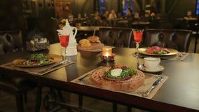 Kaars en schotel in het restaurant op de lijst stock video