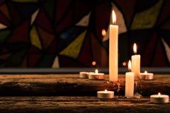 Kaars op een oude eiken houten lijst De mooie achtergrond van Gebrandschilderd glasvensters Het concept van de godsdienst Boek en royalty-vrije stock afbeeldingen