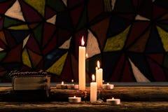 Kaars op een oude eiken houten lijst De mooie achtergrond van Gebrandschilderd glasvensters Het concept van de godsdienst Boek en stock fotografie