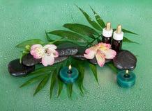 Kaarsen, aromaolie, stenen en bloemen Stock Foto