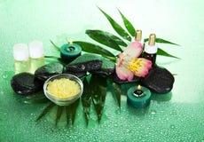 Kaarsen, aromaolie, zout, stenen en bloem Stock Foto