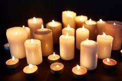 Kaarsen die in duisternis over zwarte achtergrond branden stock afbeeldingen