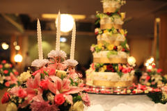 Kaarsen en bloemboeketten dichtbij huwelijkscake Stock Afbeelding