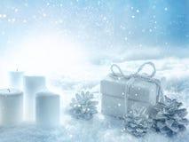 Kaarsen en een gift in de sneeuwwinter stock fotografie