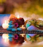 Kaarsen en toren witte stenen en handdoek, spons en zout op water Stock Foto's