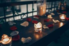 Kaarsen op de achtergrond van bloemblaadjes van rozen stock afbeeldingen