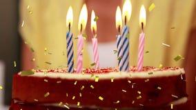 Kaarsen op een een verjaardagscake en confetti stock videobeelden