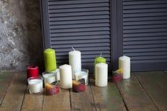 Kaarsen van verschillende bloemen en vormentribune op een vloer dichtbij stock fotografie
