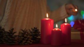 Kaarsen van weinig de aanbiddelijke meisjesverlichting op Kerstmisvooravond, geloof in gelukkige toekomst stock video
