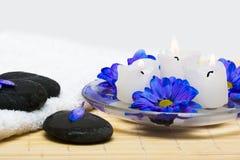 Kaarsen in water met blauwe bloemen Stock Foto