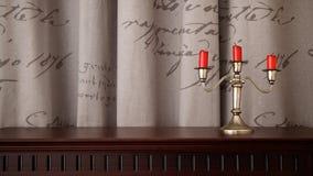 Kaarsenhouder en drie rode kaarsen Stock Foto's