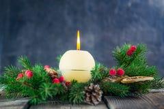 Kaart met de ronde kaars van ivoor brandende Kerstmis op komstkroon met natuurlijk decor op de oude rustieke lijst met donkere st Royalty-vrije Stock Afbeeldingen