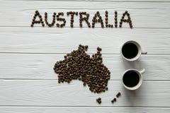 Kaart van Australië van geroosterde koffiebonen wordt gemaakt die op witte houten geweven achtergrond met twee koffiekoppen die l Royalty-vrije Stock Foto