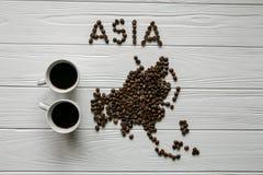 Kaart van Azië van geroosterde koffiebonen wordt gemaakt die op witte houten geweven achtergrond met twee koppen van koffie legge Royalty-vrije Stock Foto