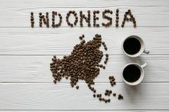 Kaart van Indonesië van geroosterde koffiebonen wordt gemaakt die op witte houten geweven achtergrond met twee koppen van koffie  Stock Foto