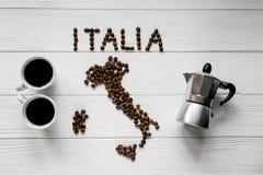 Kaart van Italië van geroosterde koffiebonen wordt gemaakt die op witte houten geweven achtergrond met twee koppen en koffiezetap Stock Afbeeldingen