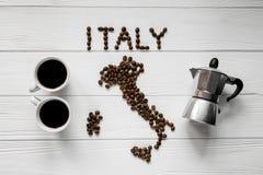 Kaart van Italië van geroosterde koffiebonen wordt gemaakt die op witte houten geweven achtergrond met twee koppen en koffiezetap Stock Fotografie