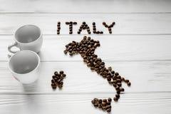 Kaart van Italië van geroosterde koffiebonen wordt gemaakt die op witte houten geweven achtergrond met twee koppen leggen die Royalty-vrije Stock Afbeelding
